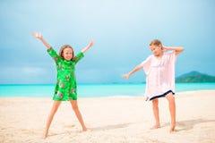 As meninas engraçadas felizes pequenas têm muito divertimento na praia tropical que joga junto Dia ensolarado com chuva no mar Fotos de Stock