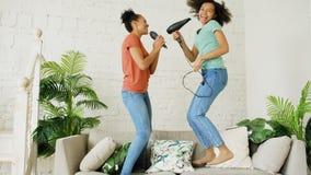 As meninas engraçadas novas da raça misturada dançam o canto com hairdryer e penteiam o salto no sofá Irmãs que têm o lazer do di foto de stock