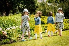 As meninas estão andando na grama em um parque foto de stock