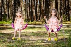As meninas estão balançando em balanços Fotografia de Stock