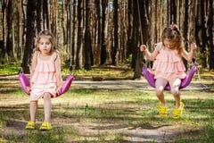 As meninas estão balançando em balanços Imagem de Stock