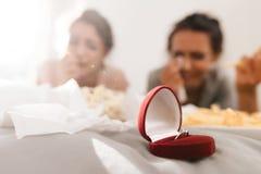 As meninas estão gritando no galinha-partido Estão encontrando-se na cama e um anel de noivado está perto deles fotografia de stock