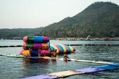 As meninas estão jogando no parque de flutuação inflável da água Imagens de Stock