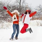 As meninas estão saltando no parque do inverno Fotos de Stock