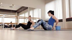 As meninas executam exercícios em uma classe aeróbia com um sorriso O instrutor da aptidão trabalha com uma menina no gym video estoque