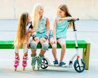 As meninas falam o assento no banco verde imagens de stock royalty free