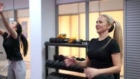 As meninas fazem exercícios em pares, jogam bolas em se Homem da aptidão training video estoque