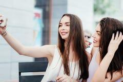 As meninas fazem um resto no café e fazem selfies Foto de Stock Royalty Free