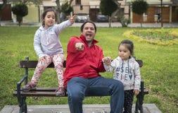 As meninas felizes apreciam o bom tempo e a luz solar Colocação das crianças e jogo bonito um com o otro e seu pai fotos de stock
