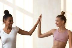 As meninas felizes diversas dão altamente cinco para o sucesso compartilhado do esporte imagens de stock royalty free