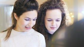 As meninas felizes do close up no tela táctil planeiam no shopping vídeos de arquivo
