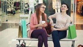 As meninas felizes estão socializando a conversa e o assento de riso no banco no shopping com à-vai bebidas e sacos de compras vídeos de arquivo