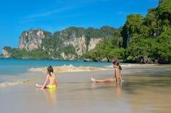 As meninas felizes jogam no mar na praia tropical Imagem de Stock Royalty Free