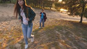 As meninas felizes viajam na floresta, monte da escalada, dão uma mão amiga Menina do caminhante caminhadas da família nas madeir video estoque