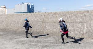 As meninas japonesas atrativas estão correndo e estão sorrindo fotos de stock