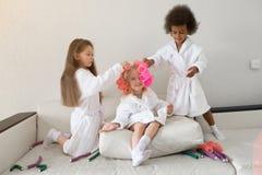 As meninas jogam com encrespadores de cabelo e gancho de cabelo imagem de stock