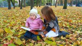 As meninas leram o livro no parque do outono Resto na natureza Fotos de Stock