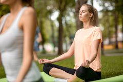 As meninas magros sentam-se nas posi??es dos l?tus que fazem a ioga sobre esteiras da ioga sobre a grama verde no parque sobre um imagem de stock royalty free