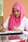 As meninas muçulmanas que escrevem um diário registram na tabela Fotos de Stock