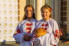 As meninas na roupa tradicional ucraniana preparam-se aos visitantes desejados Fotografia de Stock Royalty Free