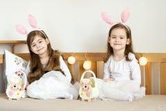 As meninas nas orelhas de coelho sentam-se no sofá com cestas da Páscoa Fotos de Stock