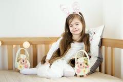 As meninas nas orelhas de coelho sentam-se no sofá com cestas da Páscoa Foto de Stock