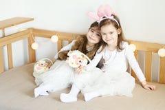 As meninas nas orelhas de coelho sentam-se no sofá com cestas da Páscoa Fotografia de Stock