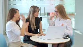As meninas no olhar do escritório no portátil e para começar a apreciar a grande notícia sobre suas realizações do trabalho vídeos de arquivo