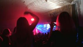 As meninas que dançam no luminoso, vídeo do concerto vivo, multidão da tomada de povos iluminados pela cor iluminam-se vídeos de arquivo
