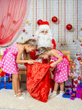 As meninas que escavam no saco com presentes que trouxeram Santa Claus Fotografia de Stock Royalty Free