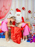 As meninas que escavam no saco com presentes Santa Claus Foto de Stock Royalty Free