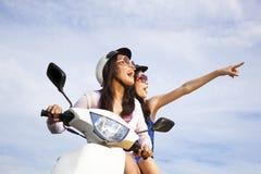 As meninas que montam o 'trotinette' apreciam férias de verão Fotografia de Stock Royalty Free