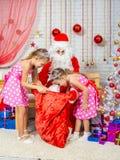 As meninas que olham um presente ensacam com presentes que trouxeram Santa Claus Imagens de Stock