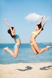 As meninas que saltam na praia foto de stock royalty free