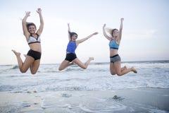 As meninas que saltam na praia Foto de Stock
