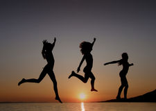 As meninas que saltam no por do sol no mar Imagens de Stock