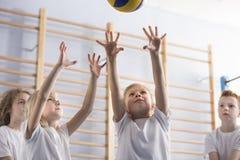 As meninas que saltam para bater o voleibol durante um jogo com sua equipe da escola acoplam-se fotografia de stock