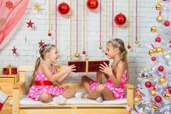 As meninas que sentam-se em um banco em uma atmosfera do Natal e mantêm o presente vermelho grande nas mãos Foto de Stock