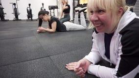 As meninas relaxam o encontro no assoalho, entre exercícios na aptidão vídeos de arquivo
