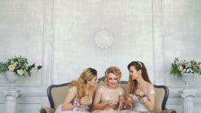 as meninas 20s sentam-se no sofá em casa e bebem-se o champanhe dos vidros filme