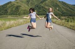 As meninas saltam na estrada que guarda as mãos Foto de Stock Royalty Free