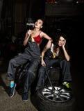 As meninas 'sexy' dos mecânicos cansados que sentam-se em uma pilha dos pneus nos reparos de um carro, uma das meninas fumam conc Fotografia de Stock