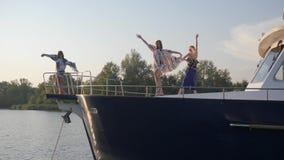 As meninas 'sexy' que dançam no movimento lento no nariz yacht e relaxam no fim de semana do verão na placa na água filme