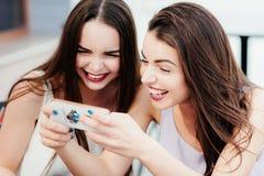 As meninas têm o divertimento com um telefone no café Foto de Stock Royalty Free