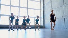 As meninas tentam repetir os movimentos na ocupação do bailado As bailarinas pequenas dançam em uma escola do bailado com panorâm vídeos de arquivo