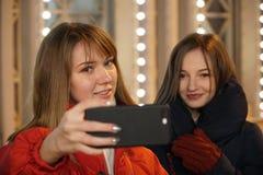 As meninas tomam um selfie no smartphone no mercado foto de stock royalty free