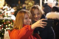 As meninas tomam um selfie no smartphone no mercado imagem de stock royalty free