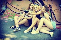 As meninas urbanas têm o divertimento com a parede próxima exterior do grunge da câmera retro da foto do vintage, imagem tonifica fotografia de stock