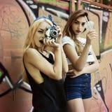 As meninas urbanas têm o divertimento com a parede próxima exterior do grunge da câmera retro da foto do vintage, imagem tonifica imagens de stock royalty free