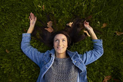 As mentiras da menina outstretched os braços na grama da esmeralda Imagens de Stock